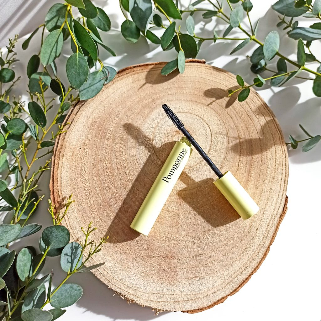 Mascara all-in-on ouvert et couché sur plateau en bois, brosse volume et longueur en picots