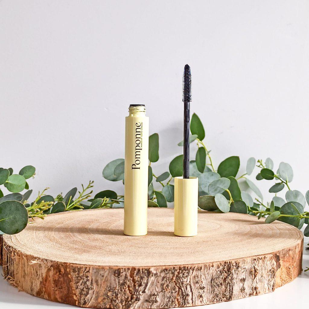 Mascara naturel booster de cils de la Pomponne debout et ouvert sur un plateau en bois